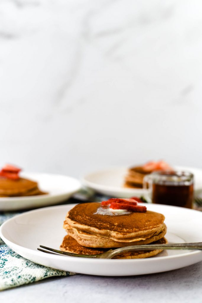 plates with stacks of strawberry pancakes and syrup jar