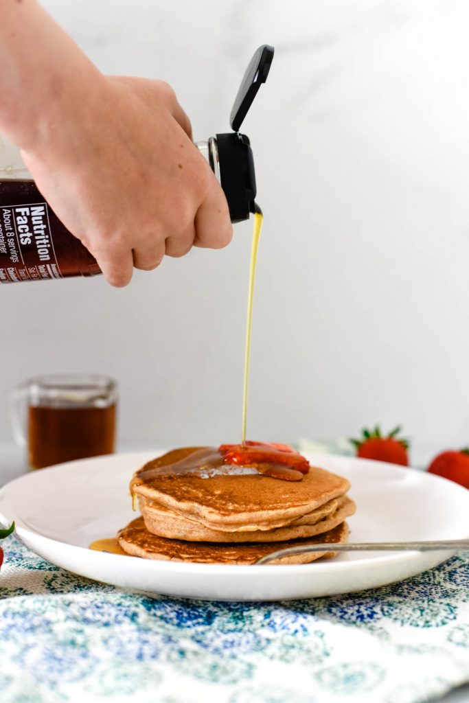 stack of pancakes with syrup being poured on