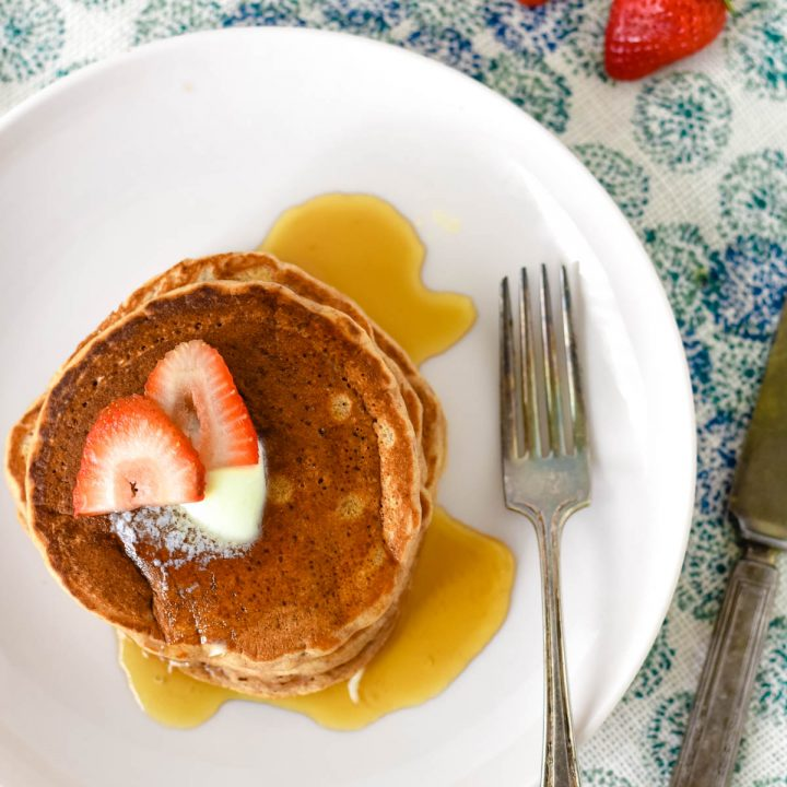 plate with strawberry pancakes with fork and napkin