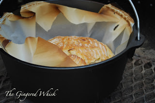 cast iron skillet with parchment paper and baked boule