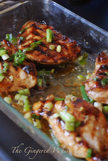 close up of grilled chicken pieces in baking dish with marinade and green onions