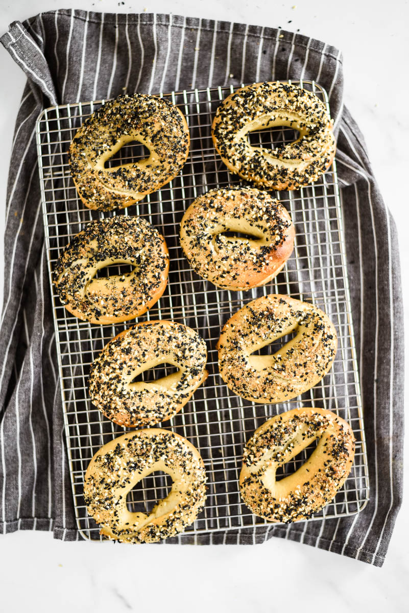 eight sourdough bagels with everything bagels topping on cooling rack with towel under
