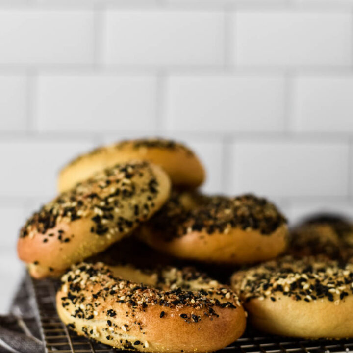 sourdough bagels piled on cooking rack