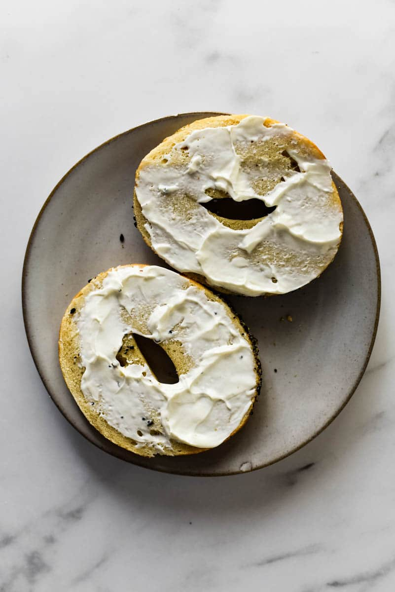 sourdough bagel cut in half and smeared with cream cheese sitting on grey plate