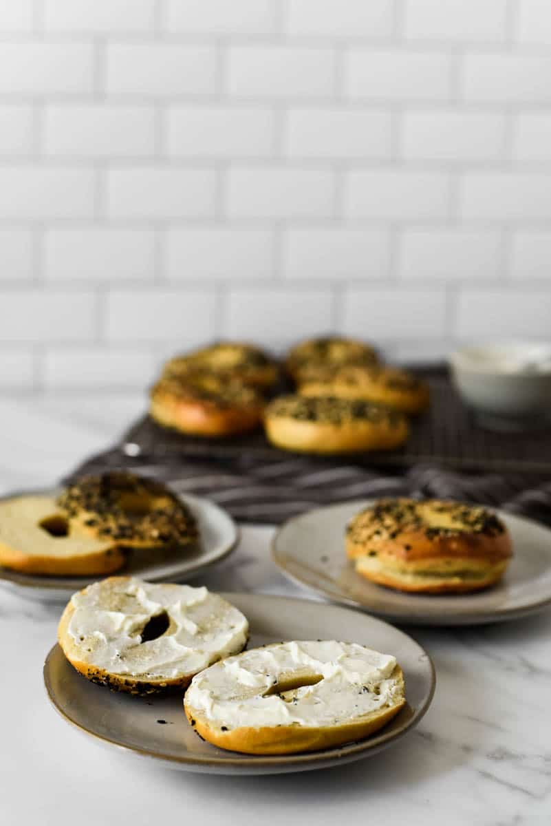 Scene with several plates with sourdough bagels, some cut, some with cream cheese, some whole