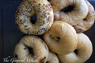 a pile of sourdough bagels with various toppings