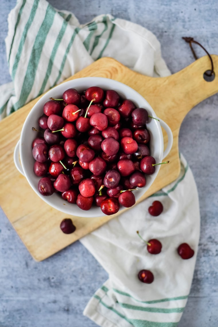 overhead view of cherries in white bowl on wooden board
