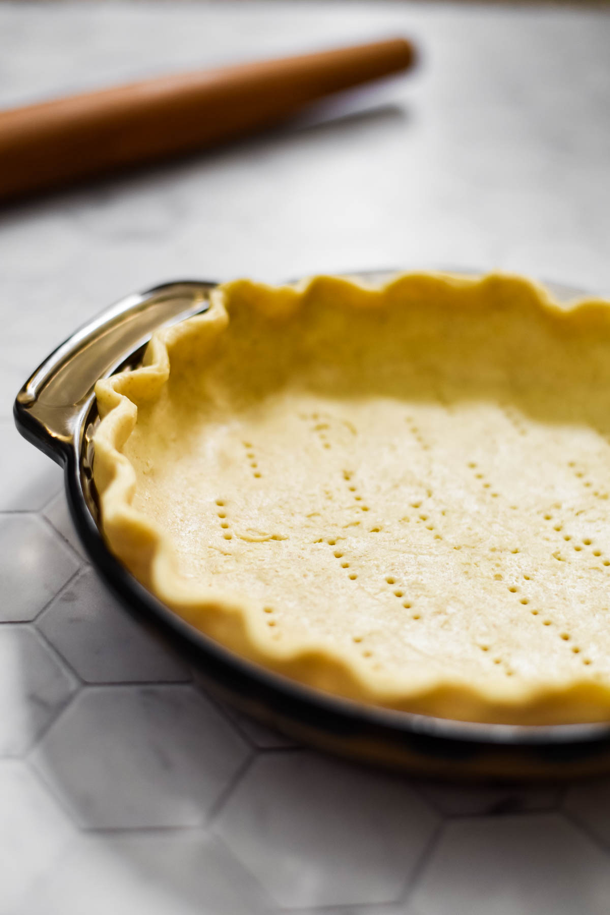 close up view of sourdough pie crust with crimped edges. Pie plate on tiled background with rolling pin in background.