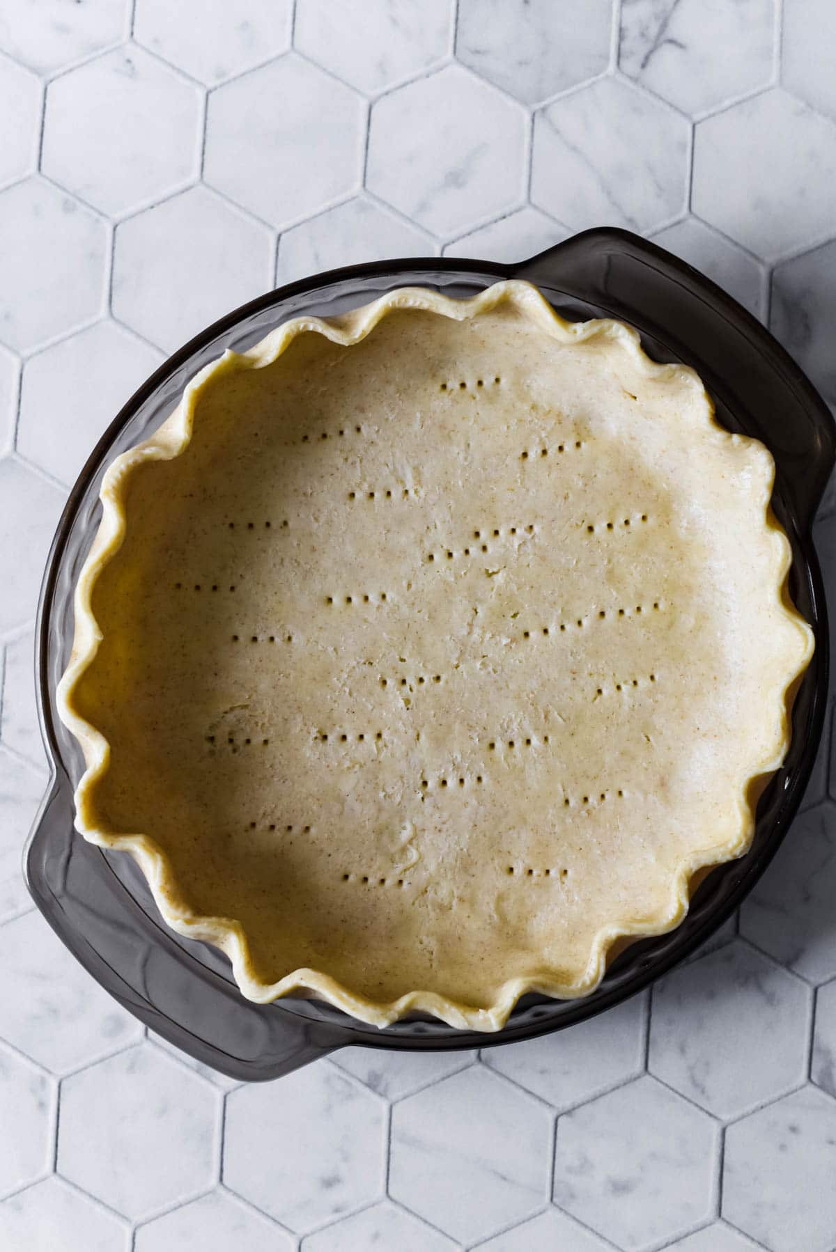 sourdough pie crust in grey glass pie plate on tiled background