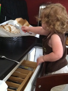 toddler sneaking on to counter to grab loaf of sourdough bread