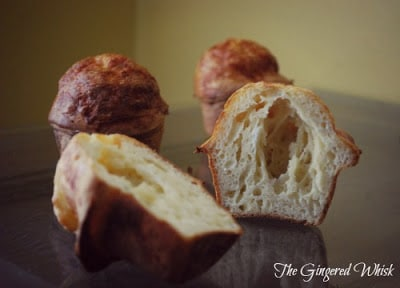 cheese sourdough popovers on table, with one split in half