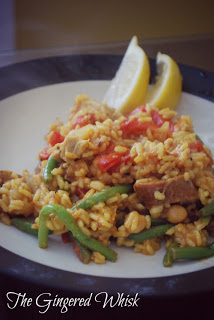 A plate of paella with chicken and sausage