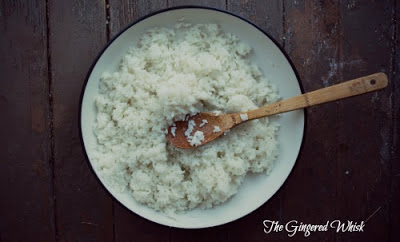 close up of bowl of white rice with wooden spoon