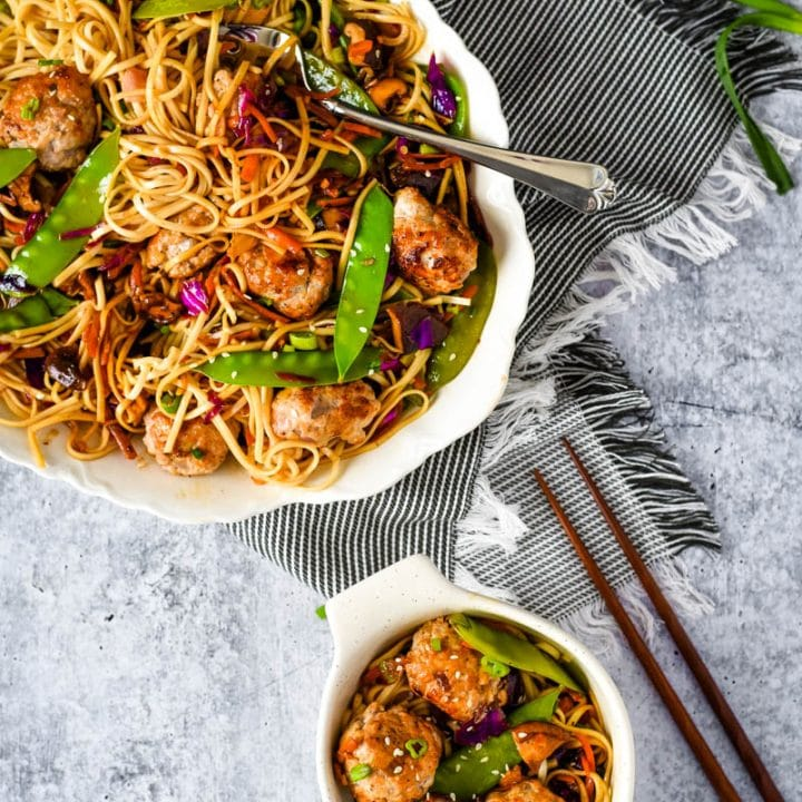 asian stir fry in white platter with meatballs and noodles