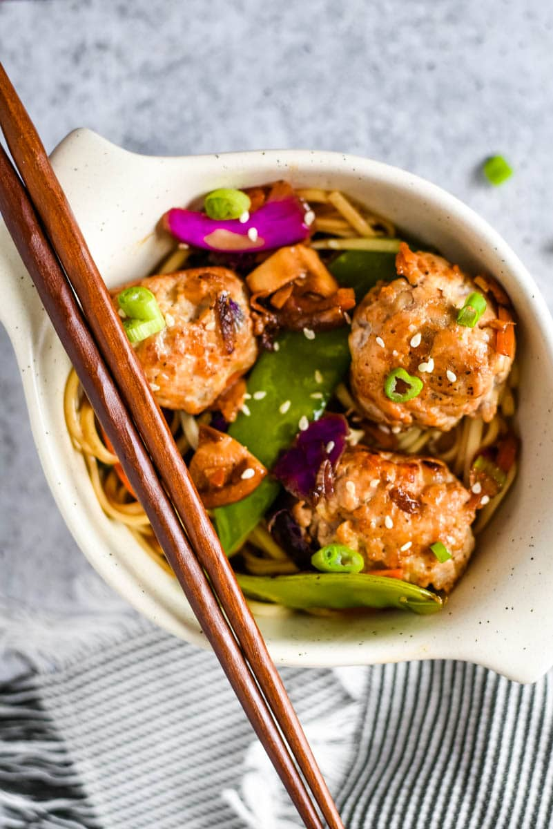white bowl with pork meatballs and udon noodles