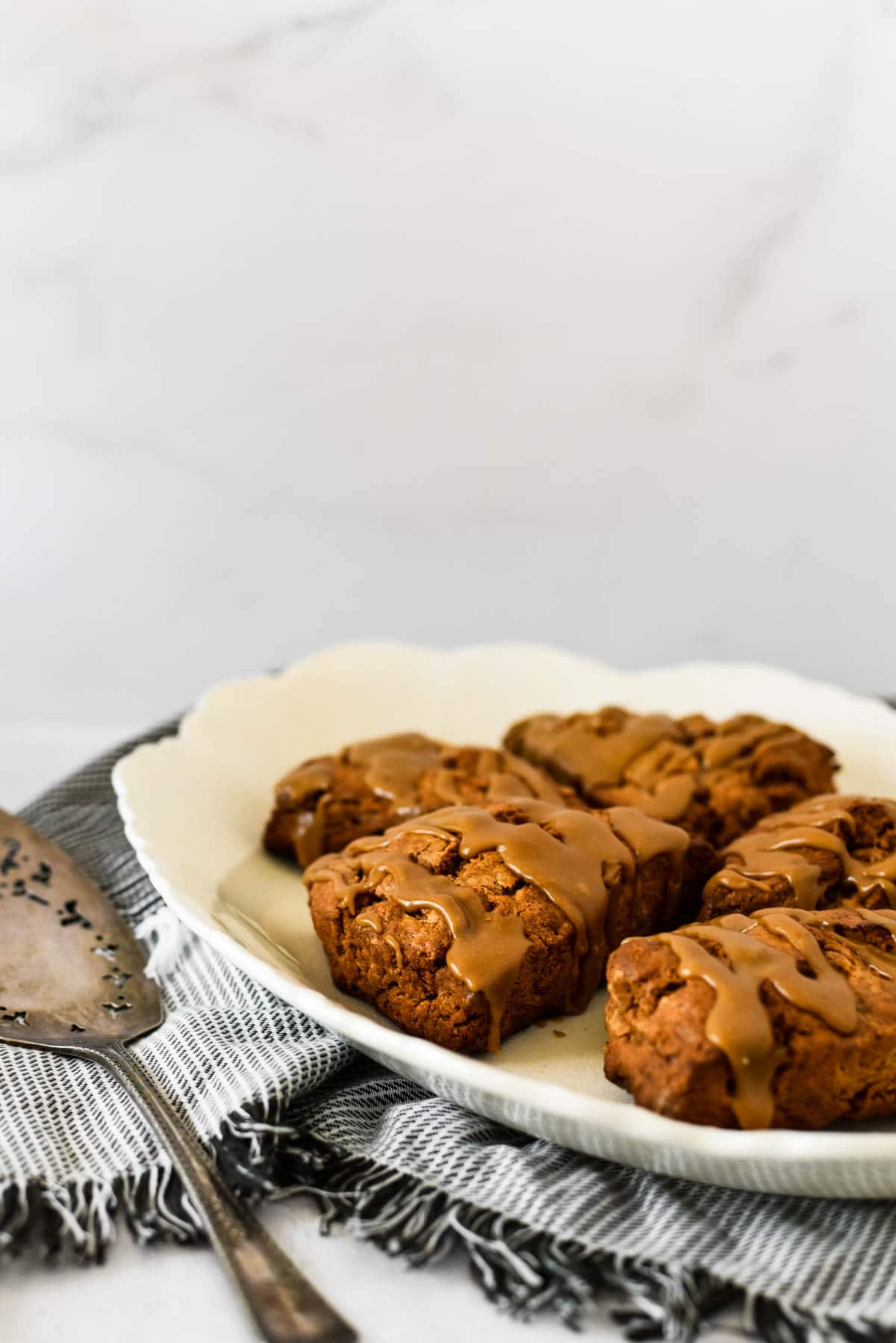 brown sugar cinnamon scones on platter with serving spatula beside