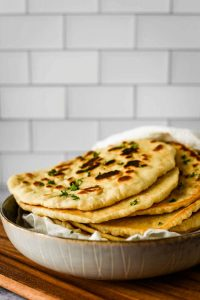 stack of sourdough naan on cutting board
