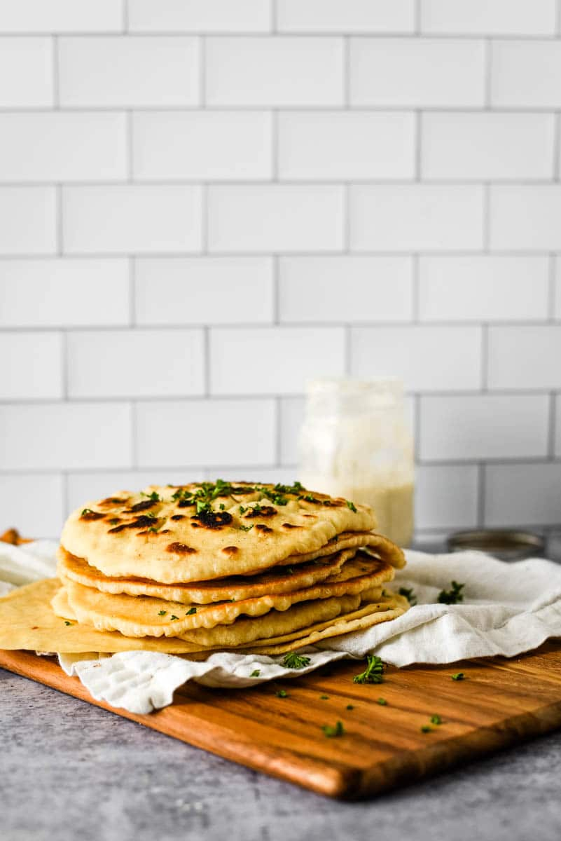 stack of eight sourdough naan beside glass jar with sourdough starter