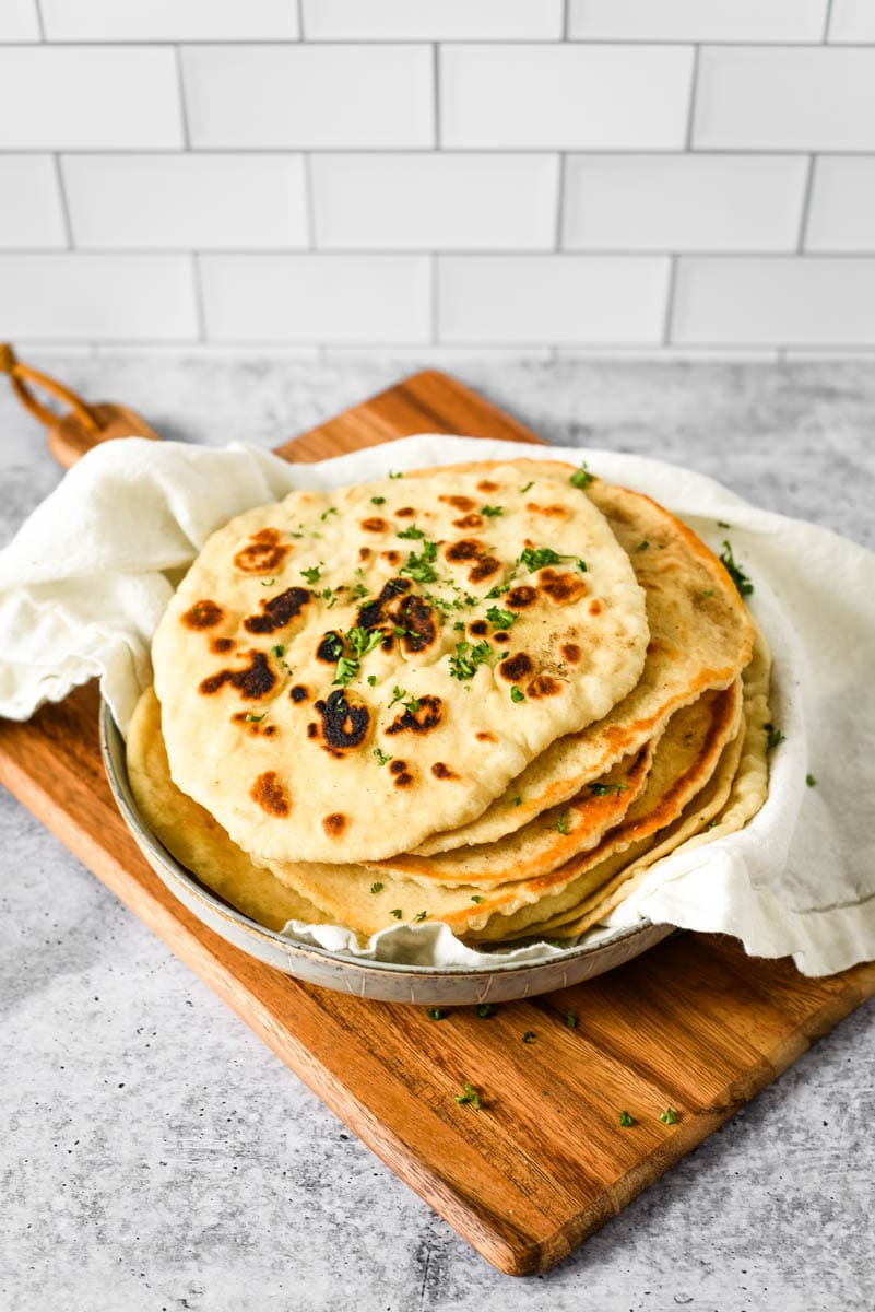 stack of sourdough naan in dish on wood board