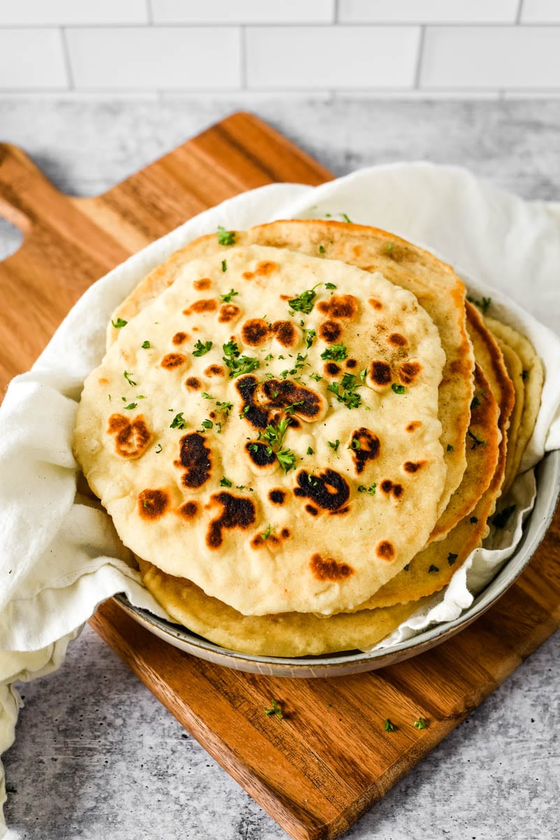 sourdough naan in bowl on wooden cutting board