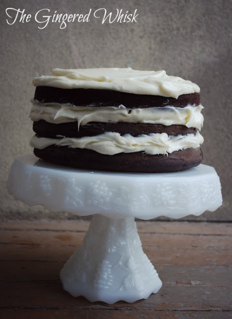 chocolate sourdough layer cake on white cake stand with vanilla frosting in between layers