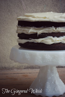 rustic chocolate sourdough cake with three layers and vanilla buttercream on white vintage cake stand