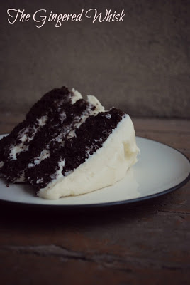 a single slice of chocolate sourdough cake on a white plate with a dark background