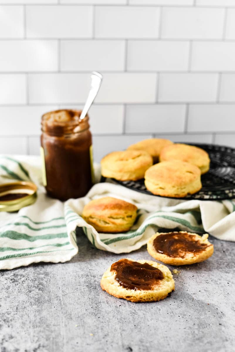 sourdough biscuits on counter, with two smeared with apple butter and jar in background
