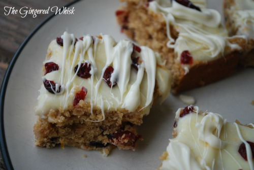 three Sourdough Cranberry White Chocolate Blondies on plate with white chocolate drizzle and dried cranberries