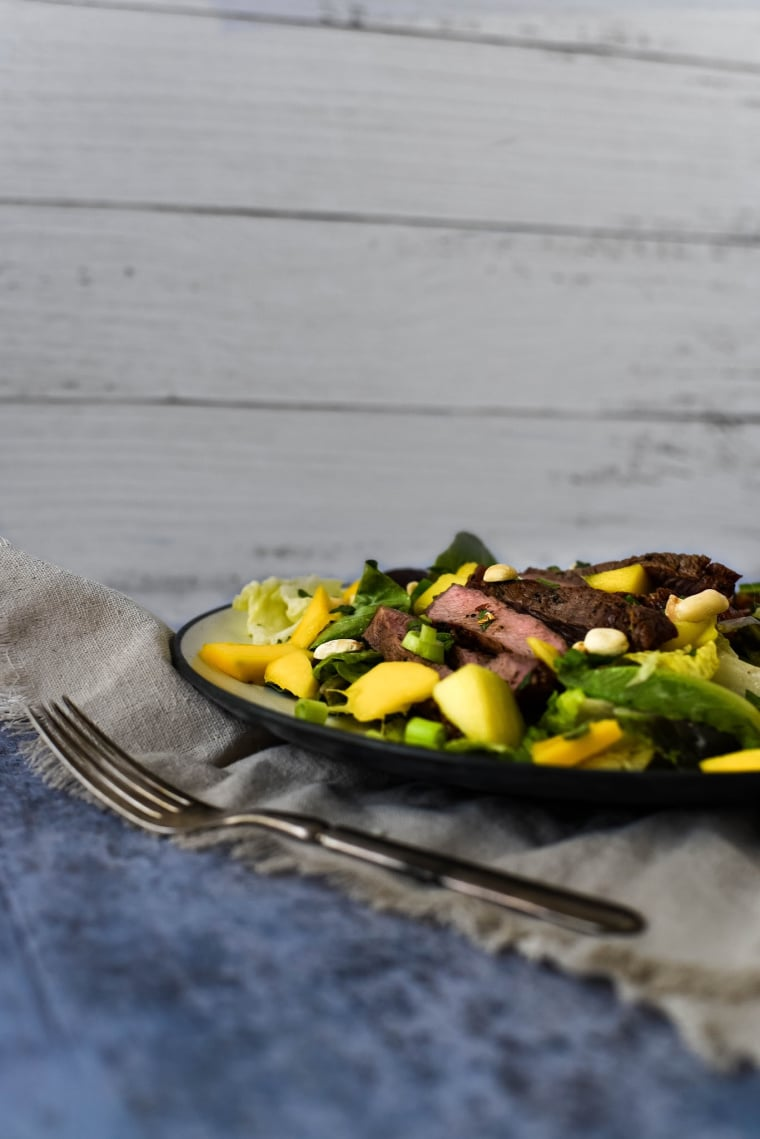 Side view of steak salad with mango
