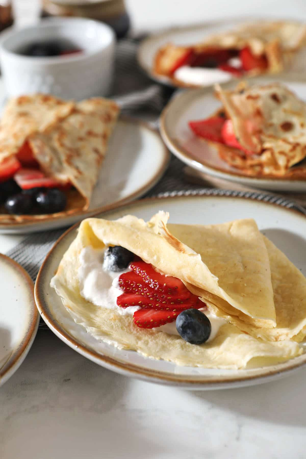 multiple plates with sourdough crepes, berries and cream