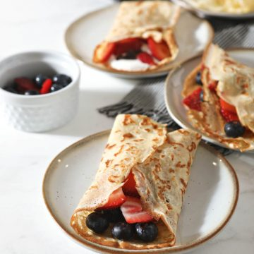 Sourdough Crepes on multiple plates with berries
