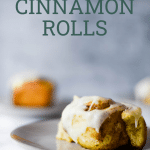 sourdough cinnamon roll on plate with text overlay for pinterest
