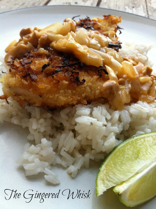 Coconut Crusted Chicken with Cashew Curry Sauce on white rice with limes