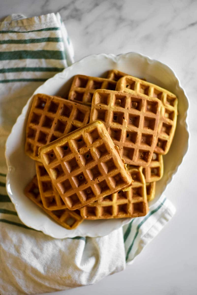 white platter piled with homemade sourdough waffles, green striped kitchen towel beside platter