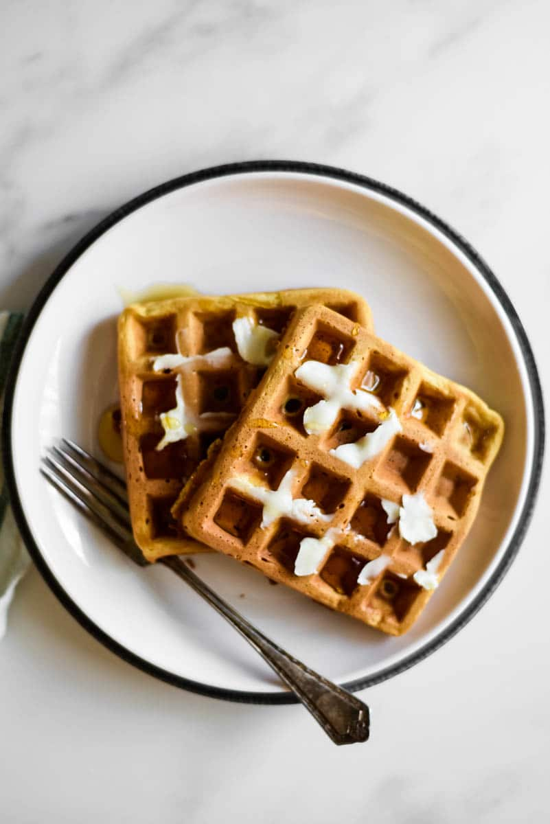 white plate with two sourdough waffles on top, smeared in butter. Fork beside the waffles