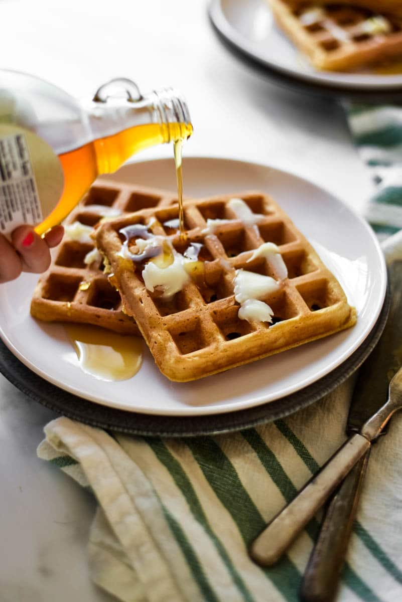 girls hand pouring maple syrup onto two sourdough waffles on white plate with silverware beside