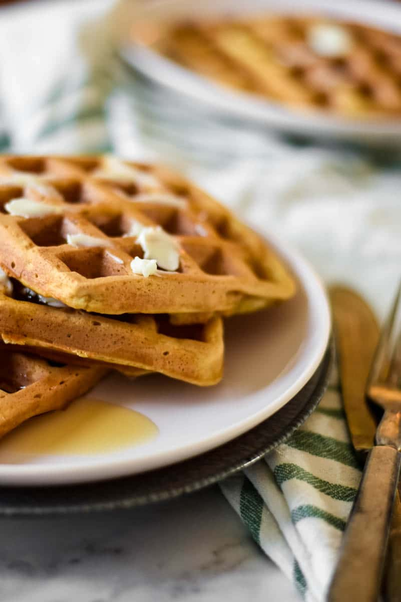 image showing two plates packed with sourdough waffles with butter and syrup