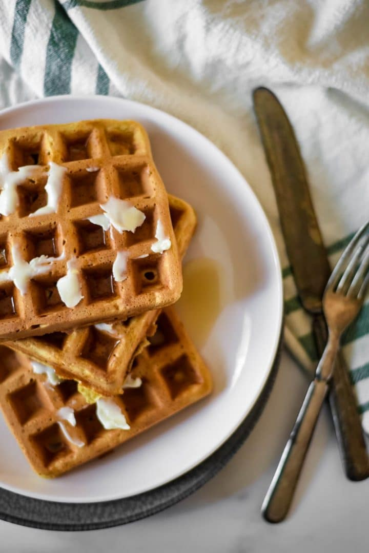 overhead view of plate of sourdough waffles with butter and syrup. Fork and knife beside plate.