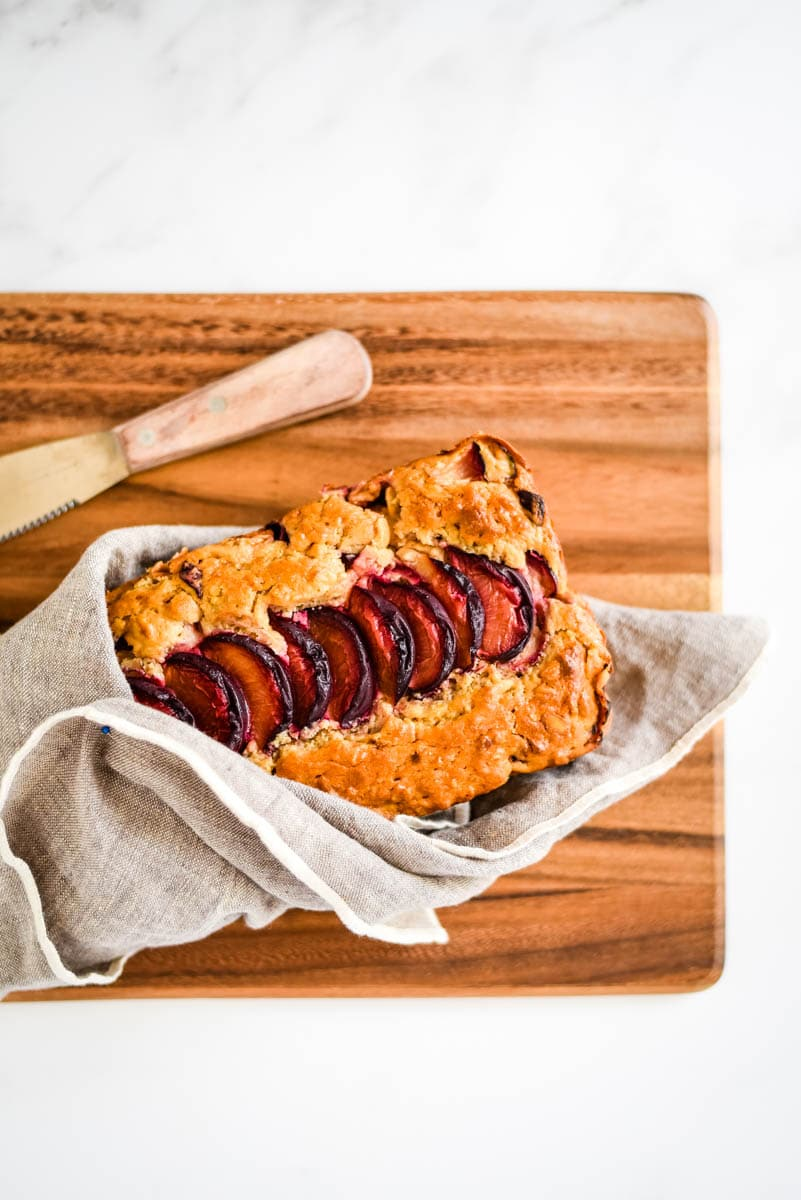 overhead view of sourdough quick bread with plums on wooden board