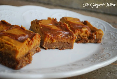 side view of Three Pumpkin Cheesecake Bars with Salted Caramel Swirls on white decorative platter