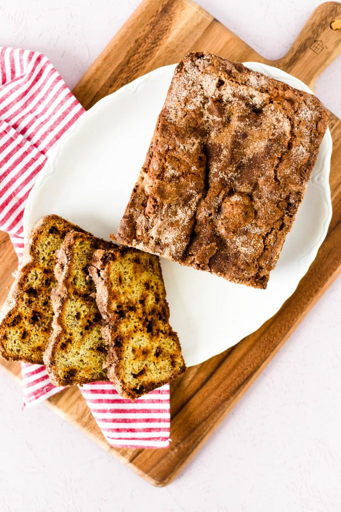 snickerdoodle banana bread loaf on platter with three slices beside it