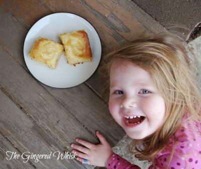little girl beside plate of lemon rolls