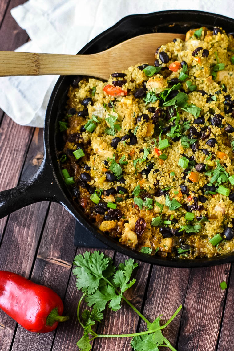 Quinoa Casserole in cast iron skillet with wooden spoon