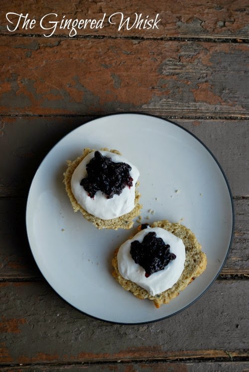 lavender and earl grey scones on white plate topped with devonshire cream and blueberry preserves