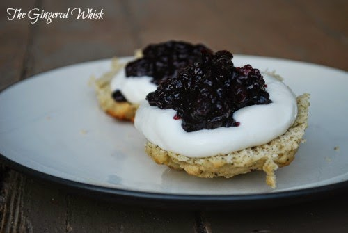 two earl grey scones on white plate with devonshire cream and blueberry preserves on top