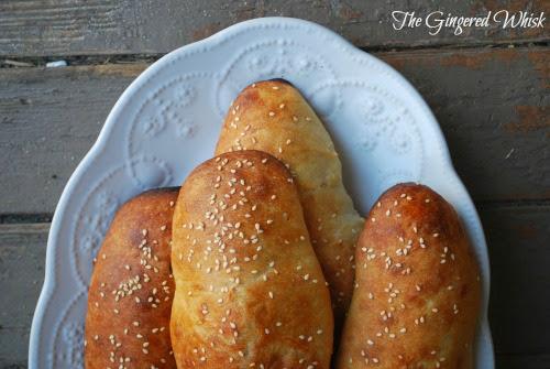 sourdough hot dog buns on white platter