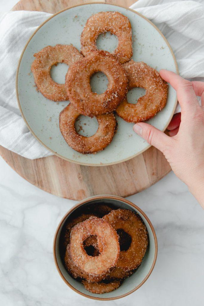 hand taking fried apple ring from platter