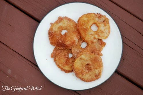 fried apples in sourdough batter rolled in cinnamon and sugar on a plate