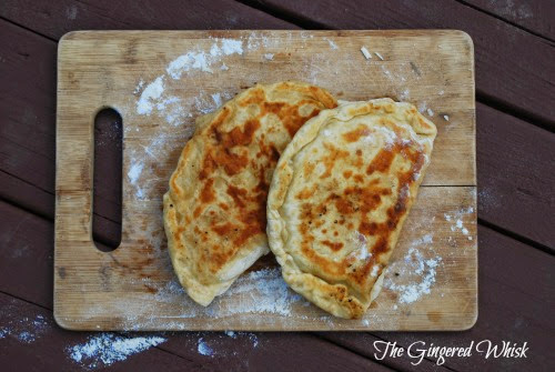 two gozleme with sourdough crust on wooden cutting board